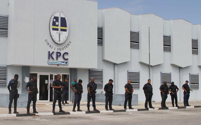 Agenten houden toezicht op betogers die zich hebben verzameld bij het bureau van het Korps Politie Curaçao. Demonstranten eisen het aftreden van minister-president Eugene Rhuggenaath vanwege de financiële problemen op het eiland.
