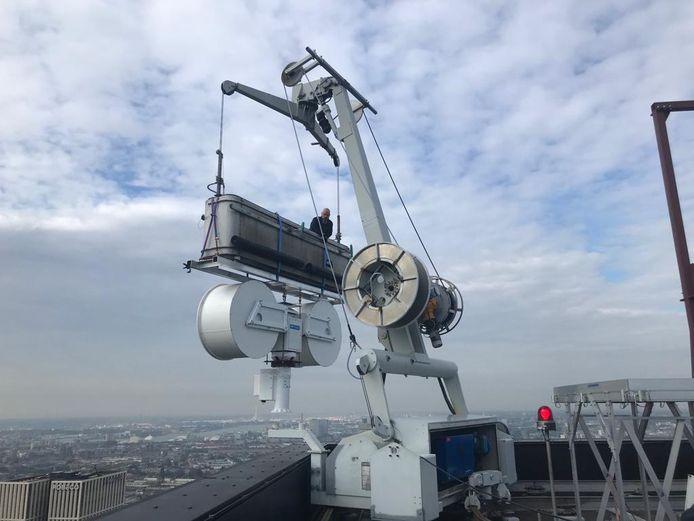 Met behulp van de glazenwasserslift word de 400 kilo wegende regenradar op het dak van de Delftse Poort gehesen.