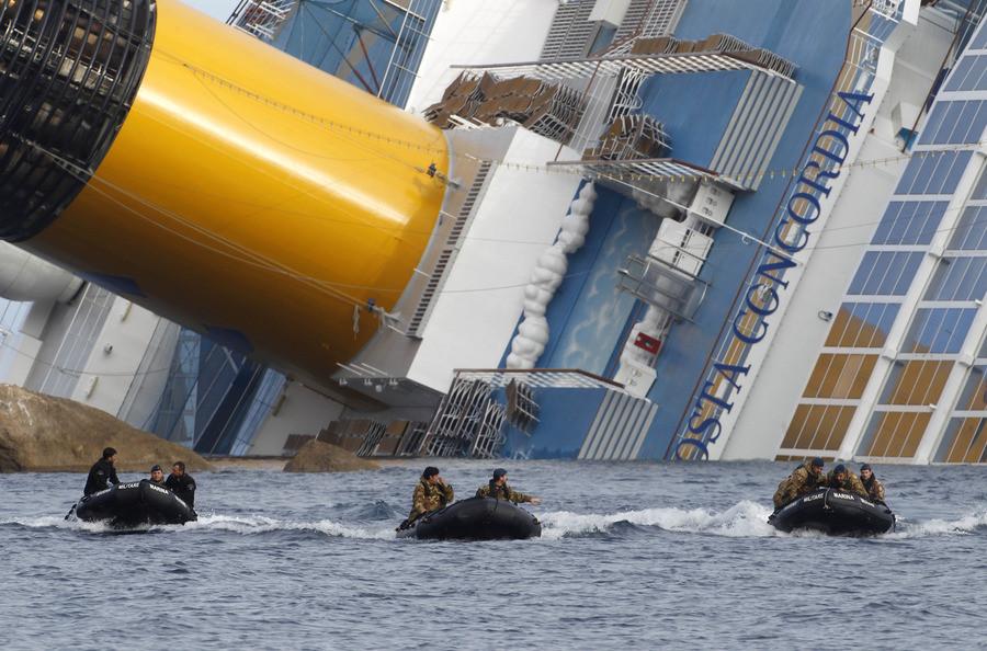 Duikers van het Italiaanse leger keren terug nadat ze in het gekapseisde schip naar overlevenden hebben gezocht.