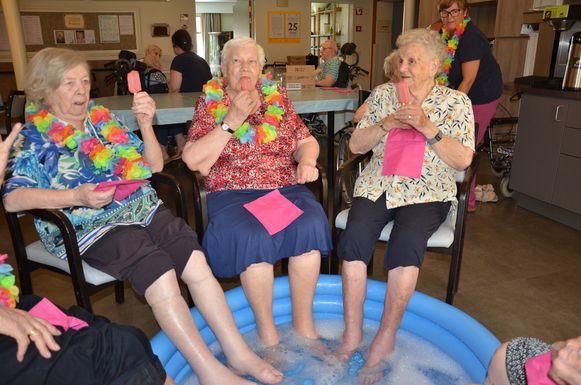 Irene (88), Reinhilde (87) en Paula (94) genieten van een ijsje terwijl ze hun voeten verfrissen in een zwembad gevuld met koud water.