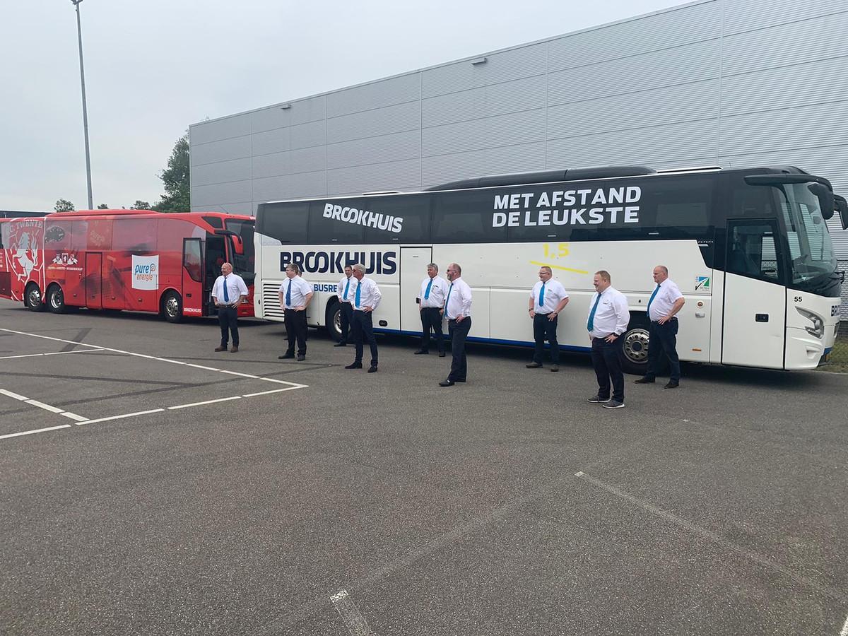 Chauffeurs van Brookhuis Busreizen klaar voor de coronatoer door de regio. De rode touringcar is de spelersbus van FC Twente