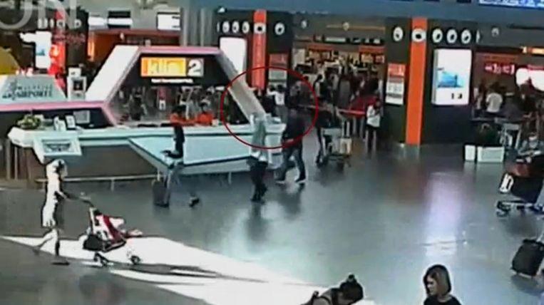 Het moment van de aanval op Kim Jong-nam op het vliegveld van Kuala Lumpur. Een vrouw in een wit shirt valt hem van achteren aan. Beeld REUTERS