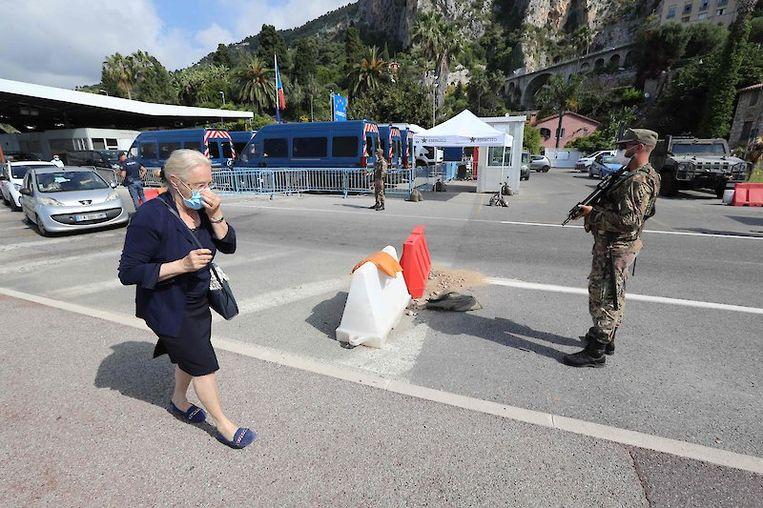 Een vrouw passeert de grens tussen Frankrijk en Italië.  Beeld AFP