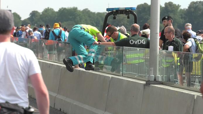 Ambulancemedewerkers buigen zich dinsdagmiddag op de Waalbrug in Nijmegen over een Vierdaagsedeelnemer die is bevangen door de hitte.