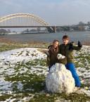 Een sneeuwpop in met op de achtergrond de Waalbrug in Nijmgen.