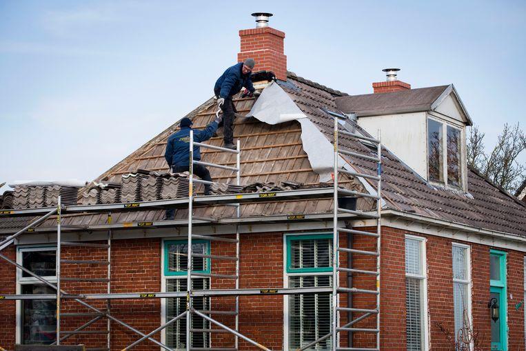 Bouwvakkers brengen een lichtgewicht schoorsteen aan op het dak van een huis in het Groningse dorp 't Zandt, om toekomstige aardbevingsschade te voorkomen. Beeld ANP