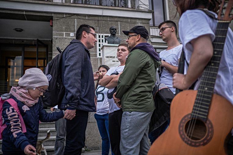 Een man (ja-stemmer) in discussie met een groep lgbt-activisten die een anti-referendumactie houden in het centrum van Cluj  Beeld Joris Van Gennip