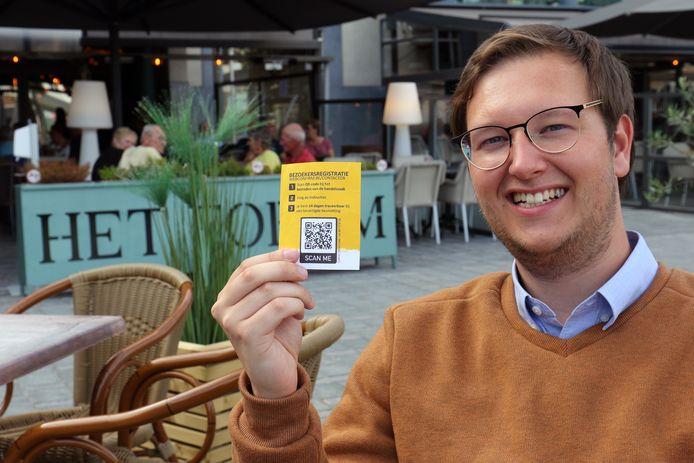 Stijn Adams toont de QR-code aan brasserie Het Forum in Geel.