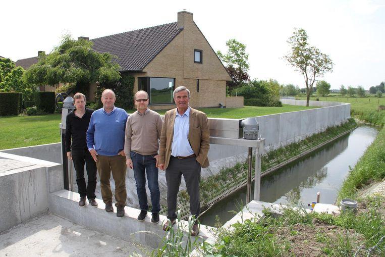 Districtingenieur Jan Desaever, schepen Walter Yde, directeur waterlopen Jan Vandecavey en burgemeester Hendrik Verkest op het stuw bij de keermuur.