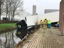 Vrachtwagen rijdt in Nijkerk tussen de bedrijven door sloot in