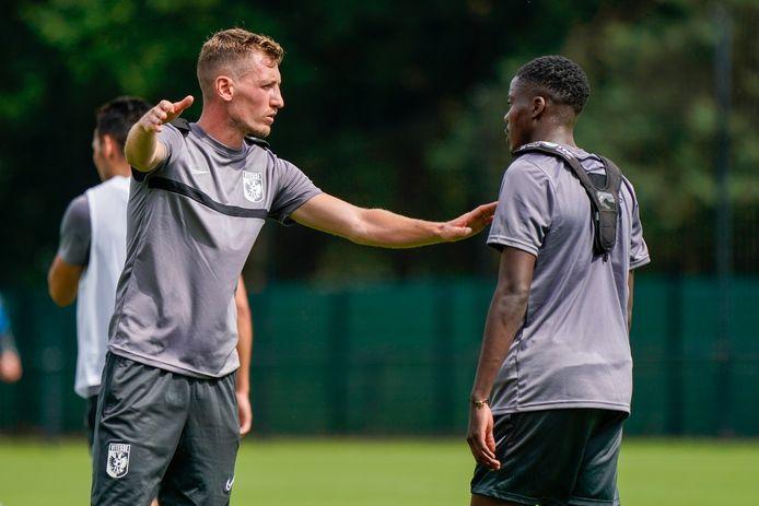 Tomas Hajek (links) praat met Richie Musaba op de training van Vitesse.