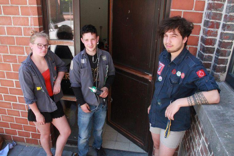 Leiders Athina Bielen (19), Christian Abbeloos (20) en Jamie Bouckenooghe (19) bij het gat in de muur en de kapotgeslagen deur die ze zelf al zo goed als mogelijk hersteld hebben.
