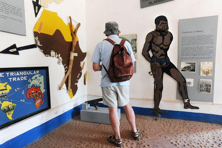 Toerist bezoekt klein museum in Juffereh, Gambia dat de slavernij behandelt.  Beeld