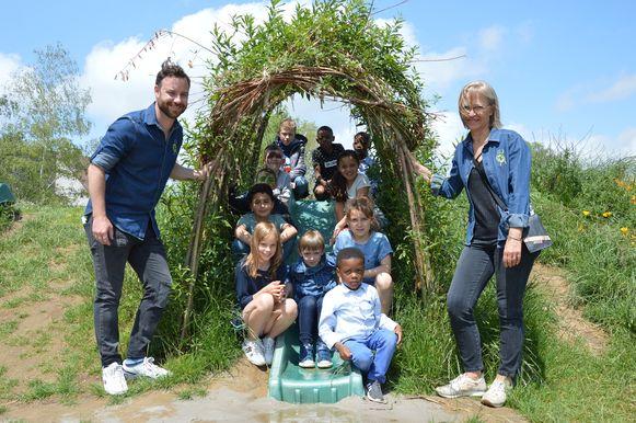 Directeur Ann Van Durme en coördinator Kevin De Leu met een aantal leerlingen op nieuwe groene speelplaats van het KCD in Denderleeuw.