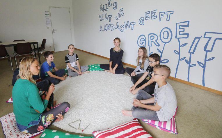 In een speciaal ingericht lokaal zitten lerares Sofie Luyens en de leerlingen in de kring.