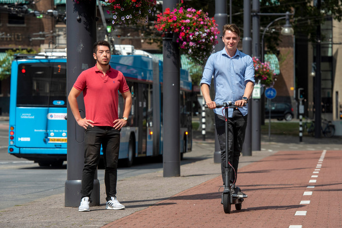 Student Max Schalow laat hem even zien op het Willemsplein: de e-step.  Links zijn collega  Chingiskhan Kazakhstan. De oprichters van het e-stepbedrijf Tulip starten binnenkort met een proef op Industriepark Kleefse Waard.
