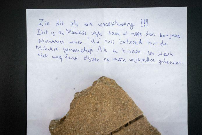 De steen en het bijbehorende briefje dat door de ruit van een woning in Elst werd gegooid.