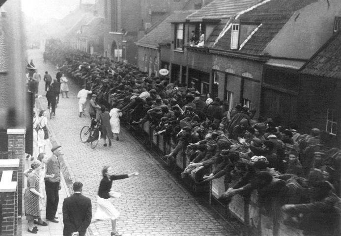 Axel mei-juni 1940: Belgische en Franse krijgsgevangenen worden door het centrum van Axel afgevoerd naar de haven van Walsoorden. Hoewel de Duitse bezetter het verbood voorzien inwoners de gevangenen van eten en drinken. fotograaf onbekend - Archief Oorlogsmuseum Gdynia, Axel