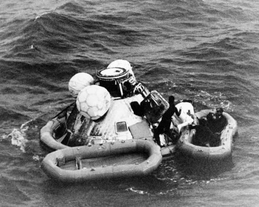 Duikers helpen de bemanning van de Apollo 8 uit de in Stille Oceaan terechtgekomen capsule.