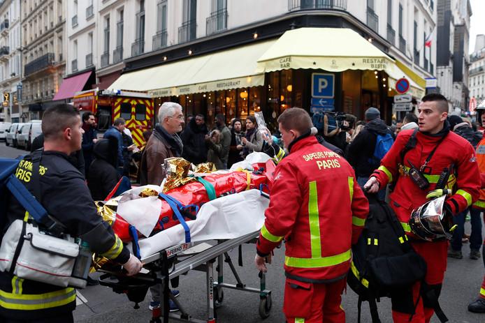 Een gewonde vrouw wordt door hulpverleners weggevoerd op een brancard.