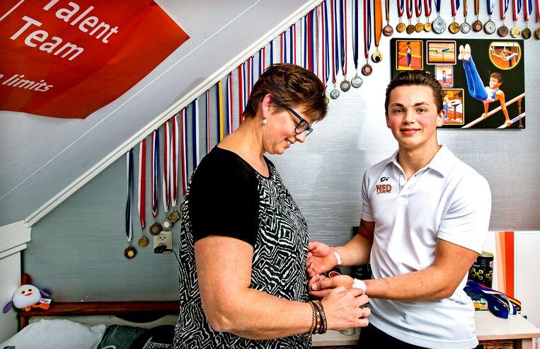 Wesley de Haas met zijn moeder Marjolein de Haas die op zijn kamer zijn polsen, die onder de eeltplekken zitten, verzorgt met een speciaal zalfje. Beeld Klaas Jan van der Weij / de Volkskrant