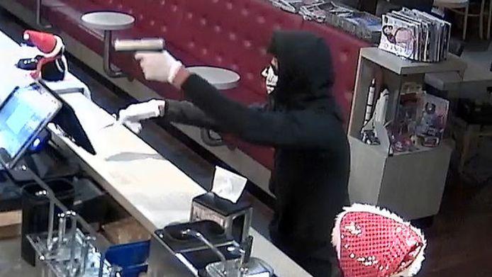 De gemaskerde dader bedreigt de bedrijfsleidster van de snackbar in Spijkenisse met een vuurwapen.
