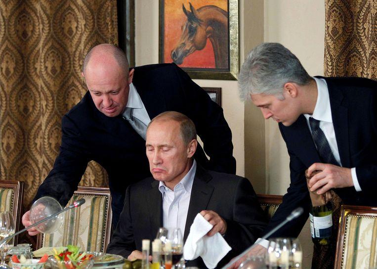 Jevgeni Prigozjin (l) serveert eten aan de Russische president Vladimir Poetin tijdens een diner in 2012. Beeld REUTERS