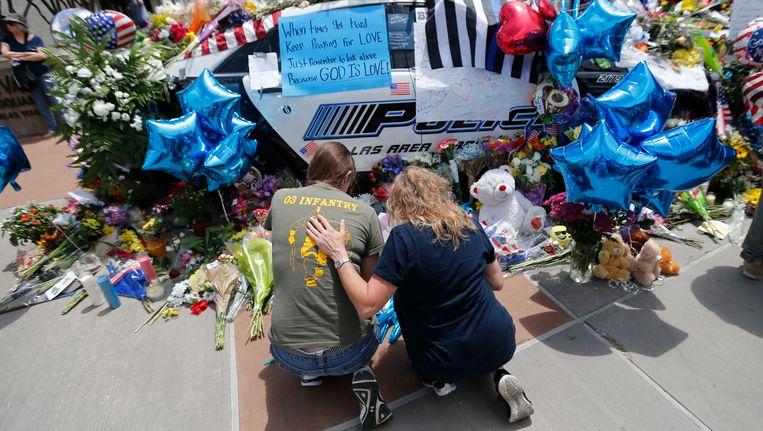 Mensen brengen bloemen naar het hoofdkwartier van de politie in Dallas. Beeld ap