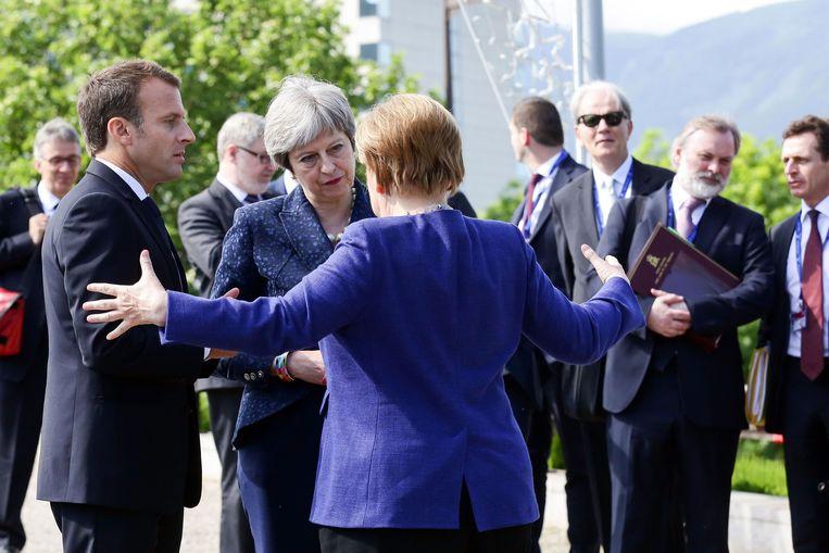 De Franse president Emmanuel Macron (links), de Britse premier Theresa May (midden) en de Duitse bondskanselier Angela Merkel. Beeld AFP
