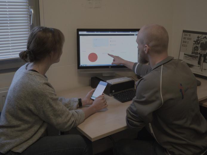 Een patiënte met lage rugpijn krijgt van haar fysiotherpeut uitleg over het gebruik van de app e-exercise.