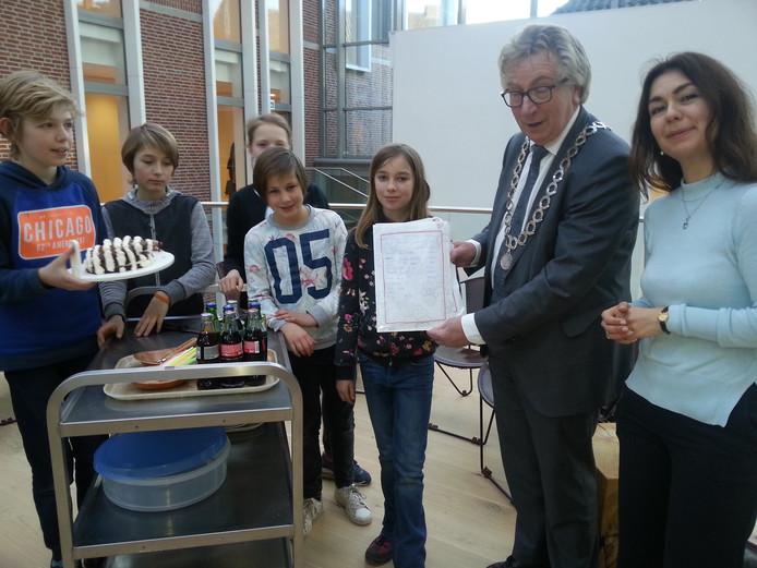 Burgemeester Geert van Rumund, met aan zijn zijde wethouder Lara de Brito, toont de Zebra Piet-petitie. Links staat Joep klaar met de Zebra Piet-taart.
