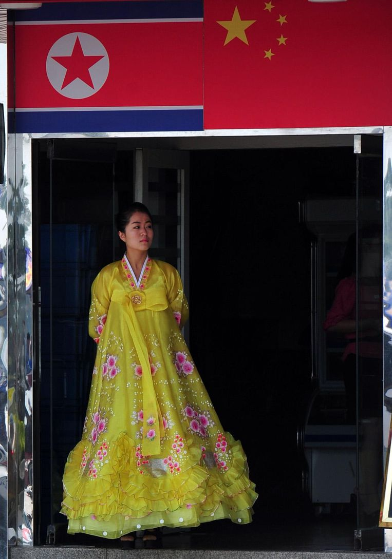 Een medewerkster staat in de ingang van een Noord-Koreaans restaurant in Dandong. Beeld Hollandse Hoogte