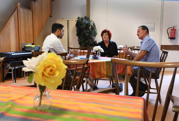 Inwoners Hans en Jans Gennissen zijn in Zoelen op het spreekuur van contactambtenaar Ranesh Balla (links). Hij ontving zijn gasten dinsdag in de koffieruimte van de kerk.