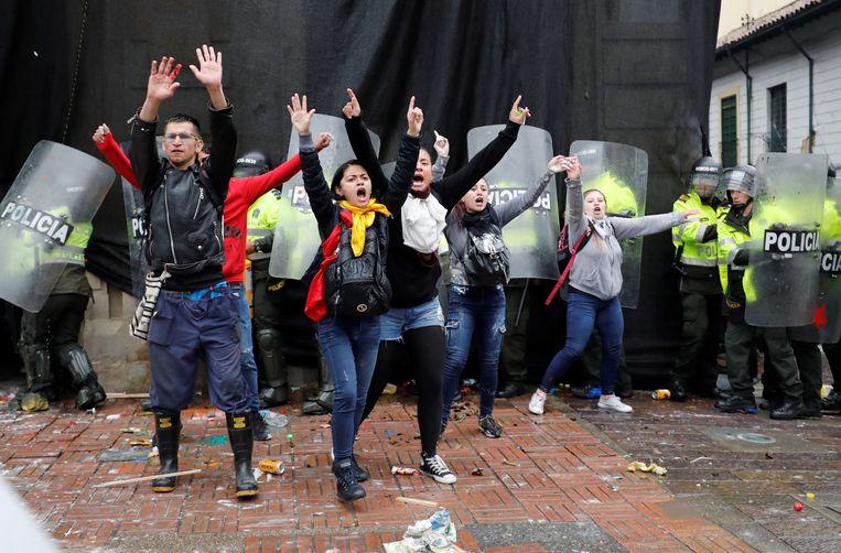 Jonge betogers op het Bolivar-plein in Bogota proberen te voorkomen dat agenten worden aangevallen.  Beeld EPA