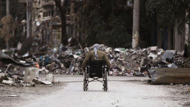 Archieffoto: Een man rijdt door de verwoeste straten van Deir Ez-Zor Beeld REUTERS