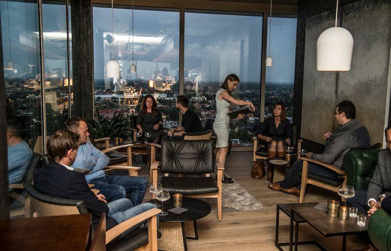Sommelier Nathalie de Baenst bedient gasten in het nieuwe restaurant Hert, met op de achtergrond het panoramisch zicht van op 70 meter hoogte