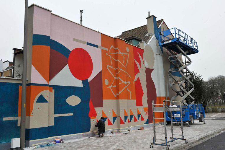 De grote muurschildering siert de volledige zijgevel van de nieuwe bushalte aan het station.