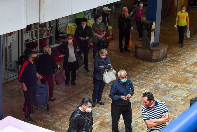 Mensen met mondkapjes in de rij voor een supermarkt in Skopje. Beeld EPA