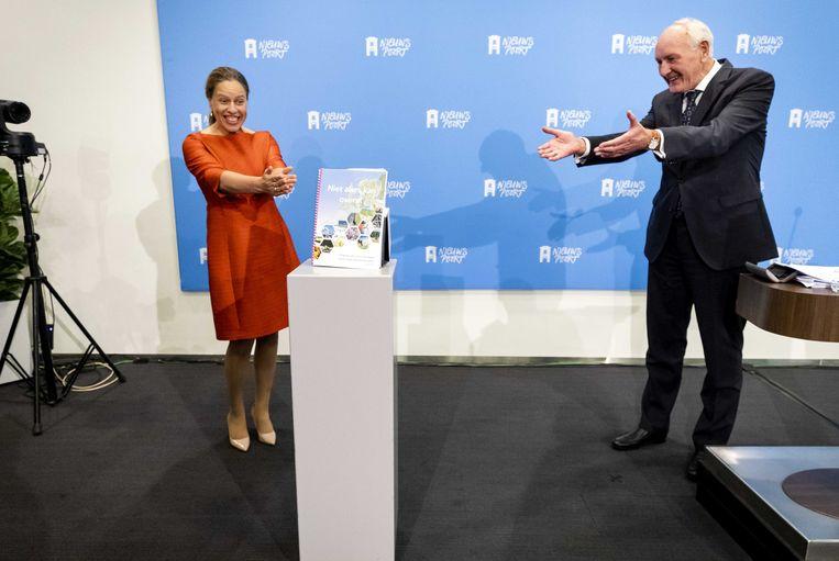 Commissievoorzitter Remkes (rechts) overhandigt op coronaveilige wijze maandag het rapport aan minister Schouten.  Beeld Sem van der Wal / ANP