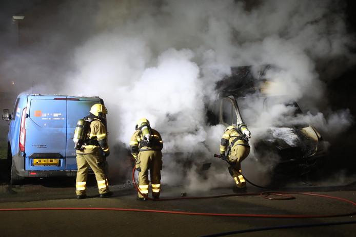 De brandweer probeert de brand in de drie bestelbusjes in Oss te bedwingen.