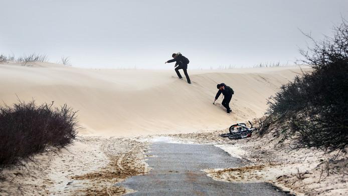 Twee jongens beklimmen het duinzand dat aan de wandel is gegaan.