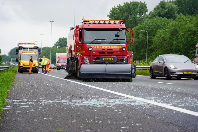Veegwagen ruimt glas en hout op nadat een vrachtwagen de lading verloor op de A27 bij Hank.