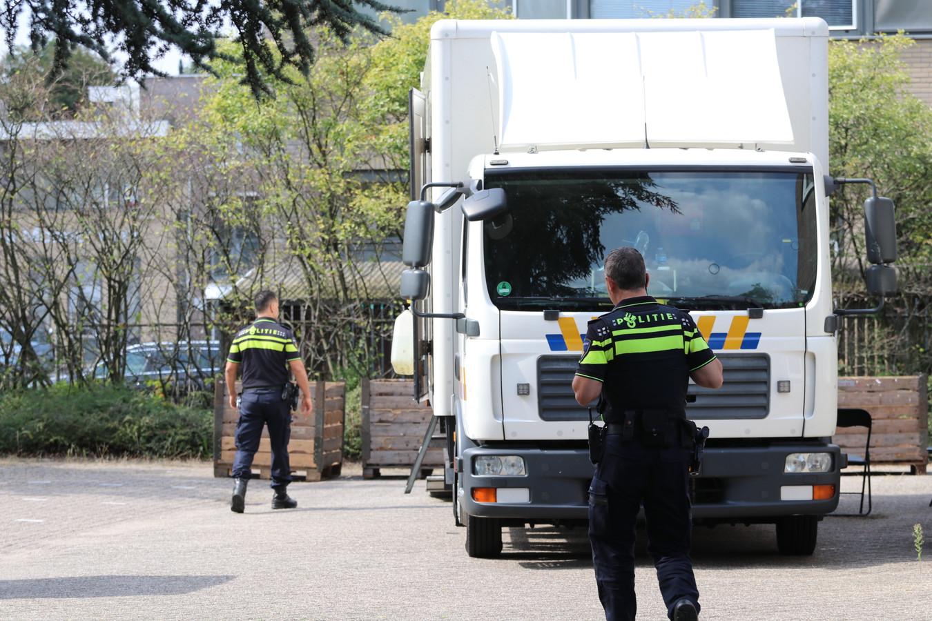 Een speciaal hennepteam van de politie haalt de planten weg uit het kantoorpand in Apeldoorn.