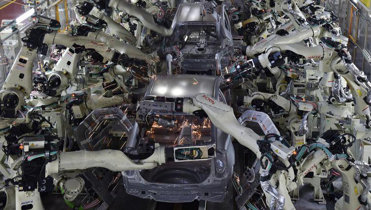 De werkplaats waar robots de carrosserie van Toyota's in elkaar zetten. Beeld AFP/Getty Images