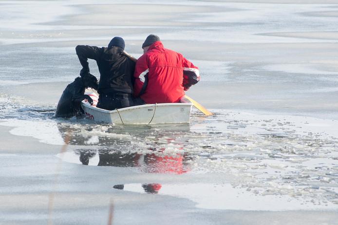 Een politieman haalt samen met een omwonende de hond uit het water.