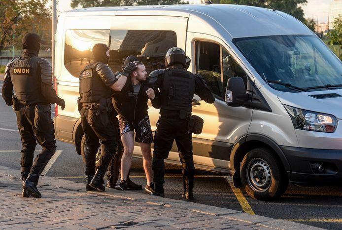 Een demonstrant in Minsk wordt aangehouden door de politie.