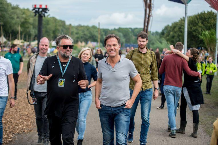 Festivaldirecteur Eric van Eerdenburg leidt premier Rutte rond tijdens Lowlands 2019. Beeld ANP