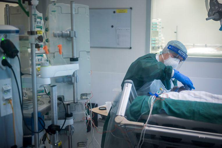 Een verpleegkundige in Essen verzorgt een covid-patiënt op de ic. Duitse ziekenhuizen over de grens met Nederland zijn ook bereid Nederlandse patiënten op te nemen.  Beeld Getty Images