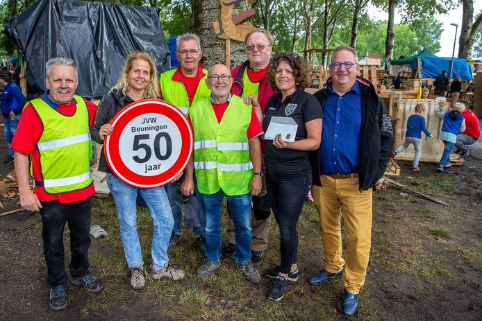 Wethouder Pim van Teffelen (rechts) heeft het 50-bord uitgereikt aan het bestuur van de stichting Jeugd Vakantieweek Beuningen. Links naast Van Teffelen Maaike van der Zande.