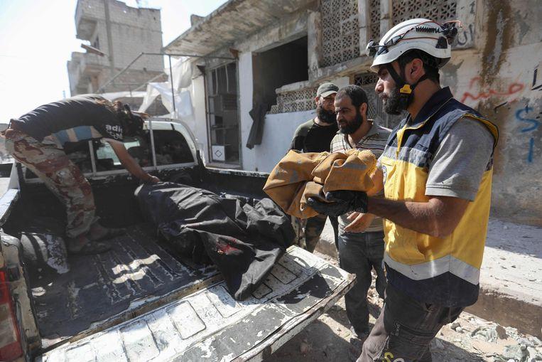 Witte helmen halen het lichaam van een vrouw en haar pasgeboren zoontje weg na luchtaanvallen op de stad Kafriya.